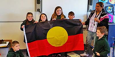 Bruthen Primary School students and teacher Nikki Hood hold an Aboriginal flag